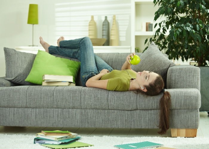 woman laying on couch eating an apple